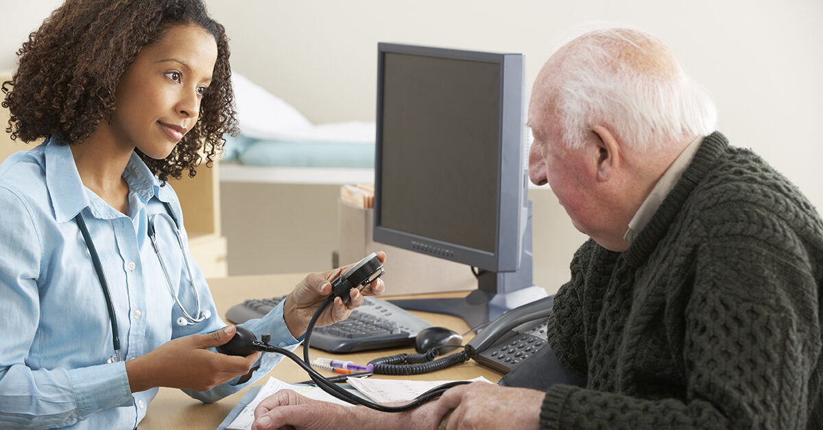 Healthcare professional taking an elderly man's blood pressure