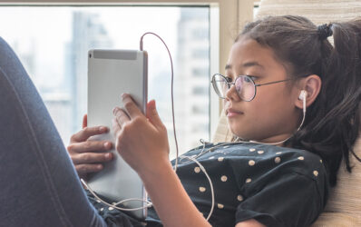 Young girl wearing earbuds using a tablet by a window