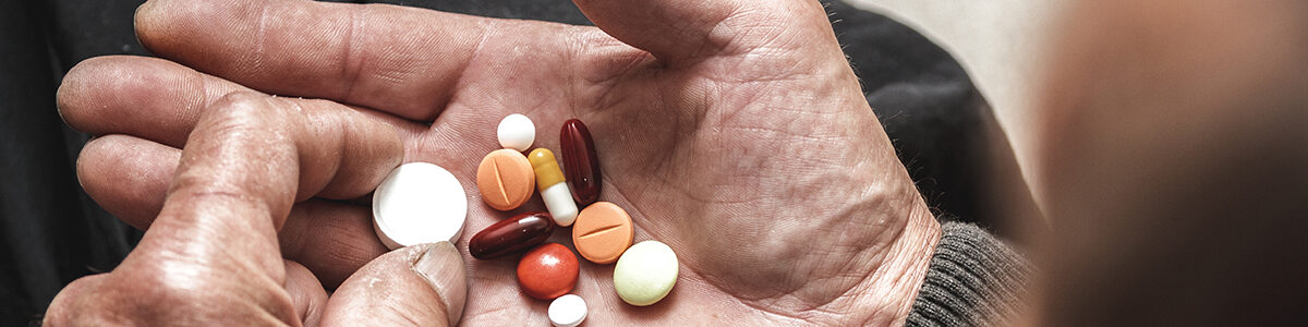 Elderly hand holding a variety of pills