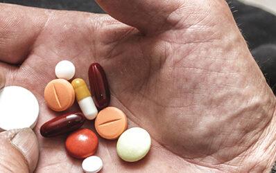 Elderly hand holding a variety of pills